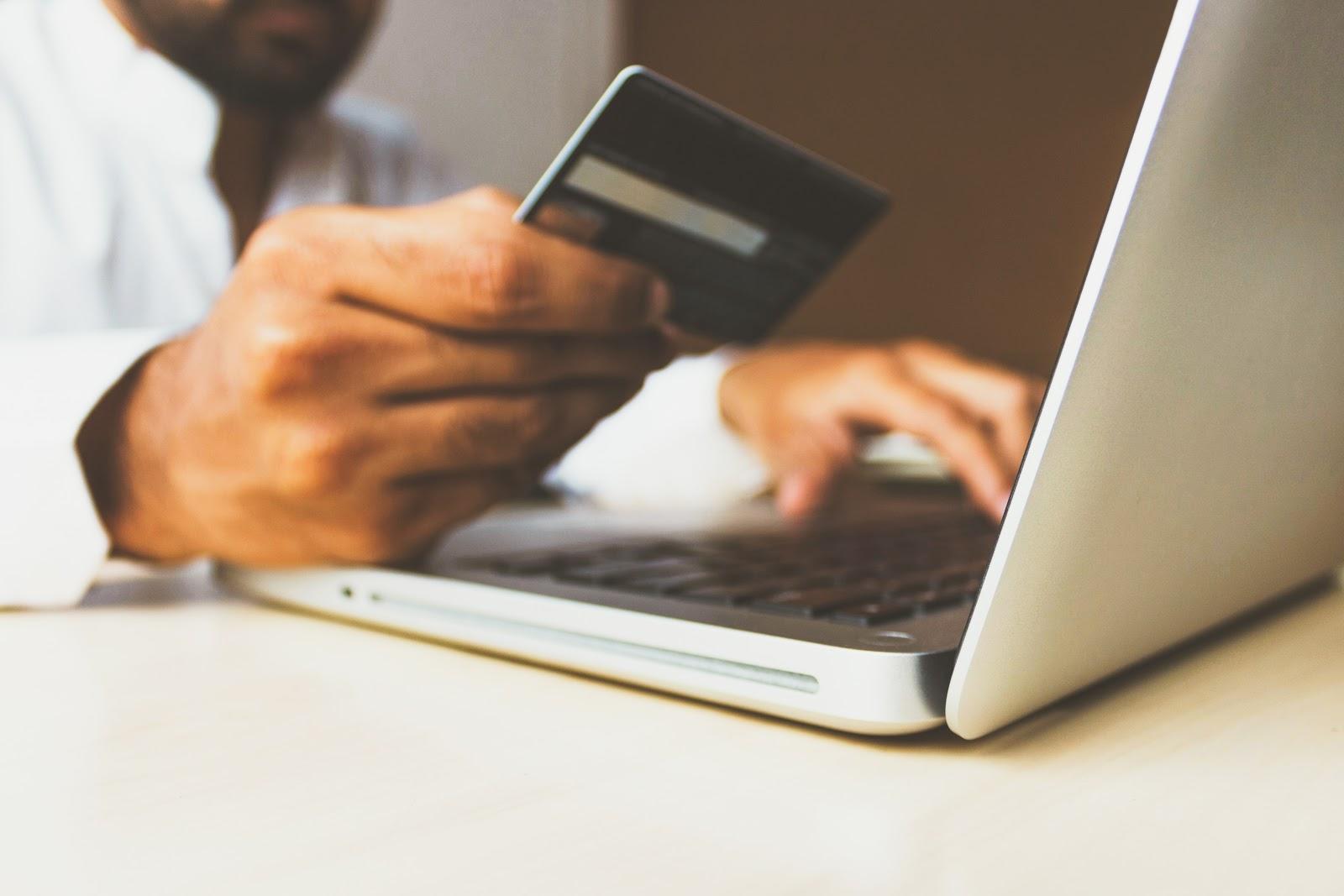 photo d'un homme effectuant un paiement en ligne sécurisé avec sa carte de crédit