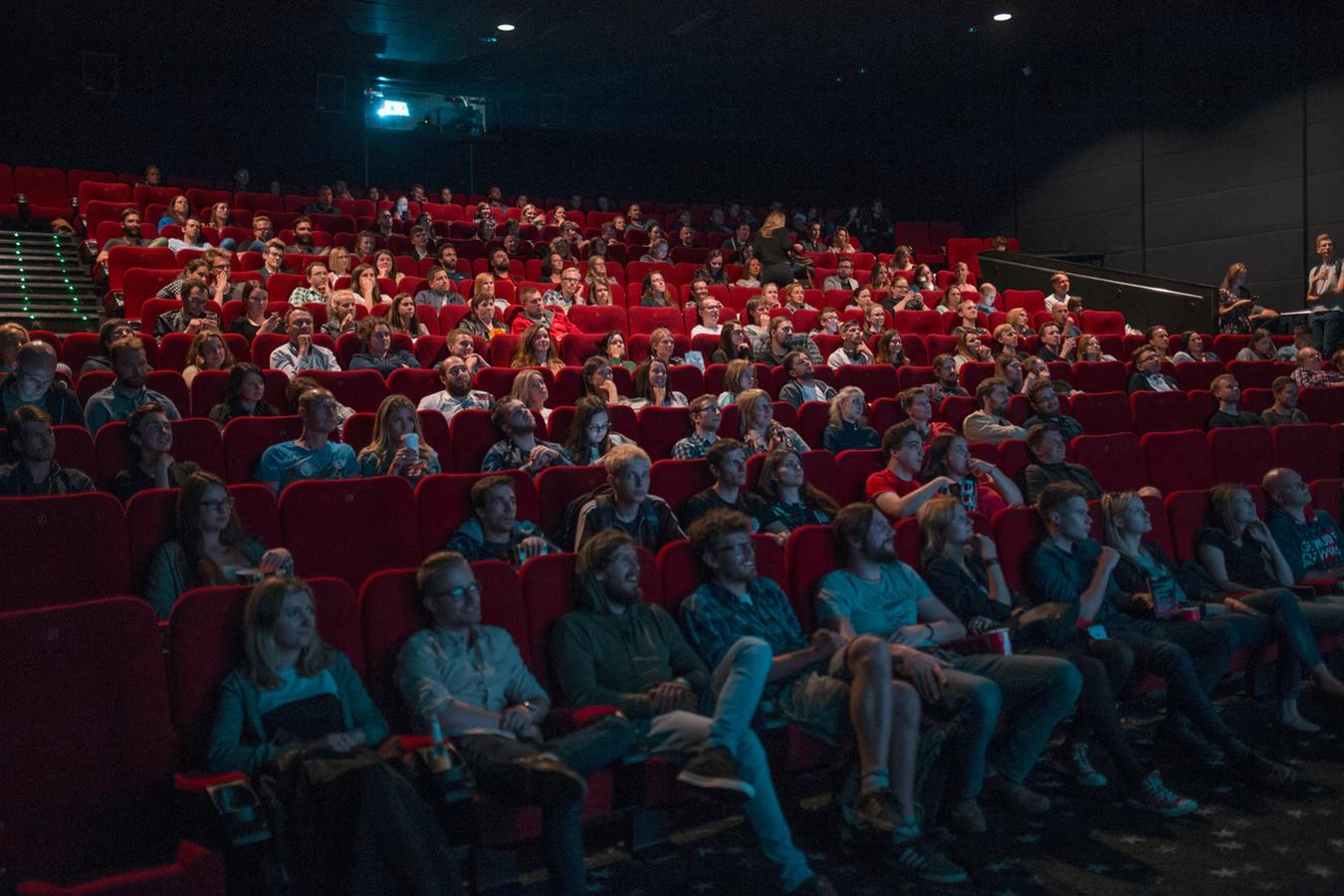 一群觀眾在電影院裡笑著看螢幕。