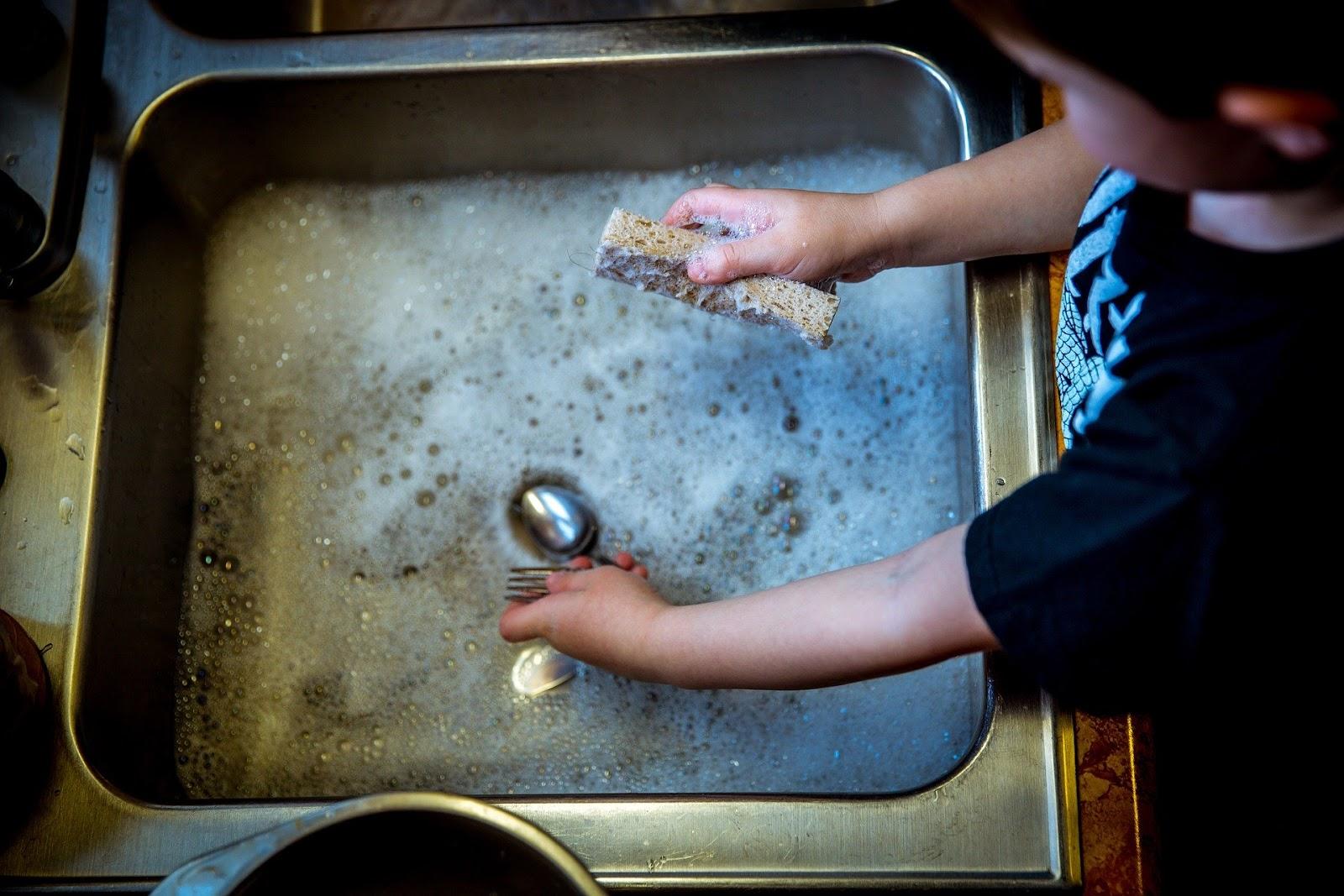ילד שוטף כלים בכיור