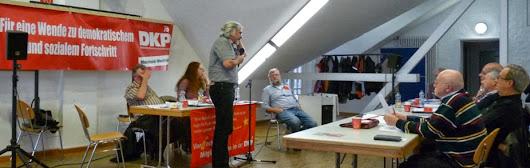 Podium, Redner am Mikrofon, Teilnehmer und Transparent: »Für eine Wende zu demokratischem und sozialen Fortschritt. DKP«.