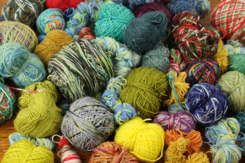 a pile of multicoloured ends of yarn. most are dishevelled little balls