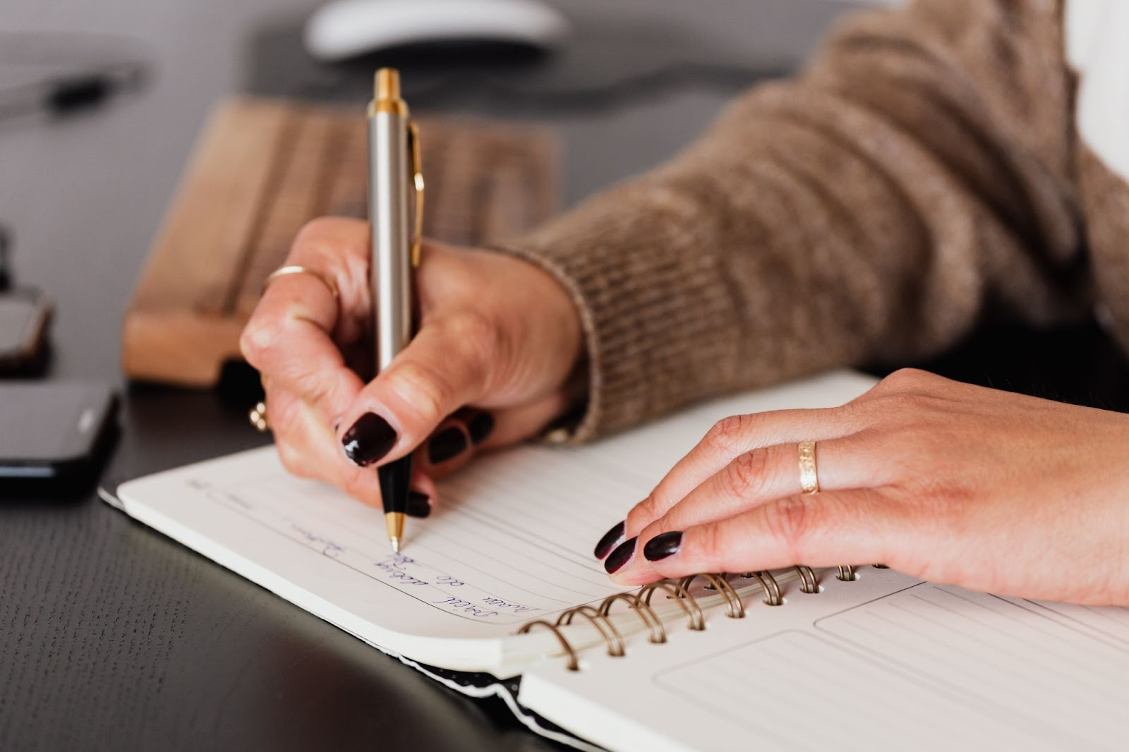 A woman is writing something in the notebook with a pen on the table.
