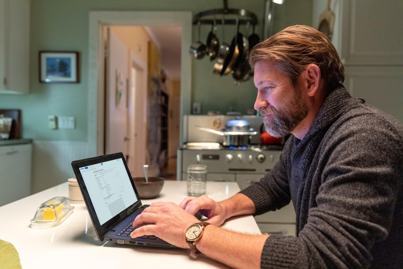 A student reviews online course material on a laptop from at their kitchen table.