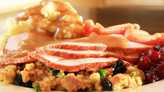 A plate of Thanksgiving dinner - turkey, potatoes & gravy, cranberry sauce, and stuffing
