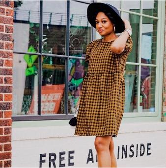 Jasmine Jones in dress and hat walking by shop window
