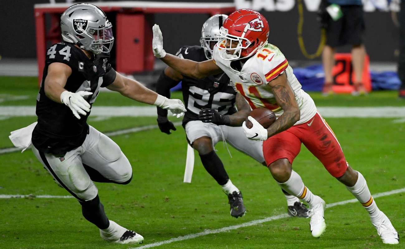 Driving wide receiver Demarcus Robinson of the Kansas City Chiefs comes up against two Las Vegas Raiders.