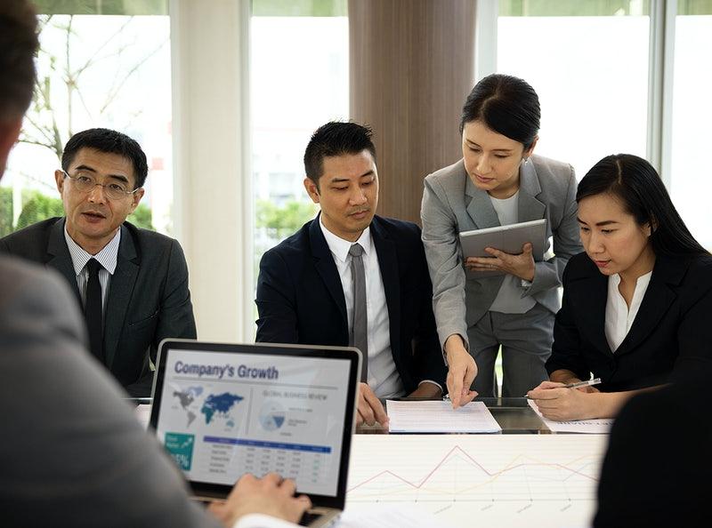 Pessoas focadas em papeladas num escritório de trabalho.