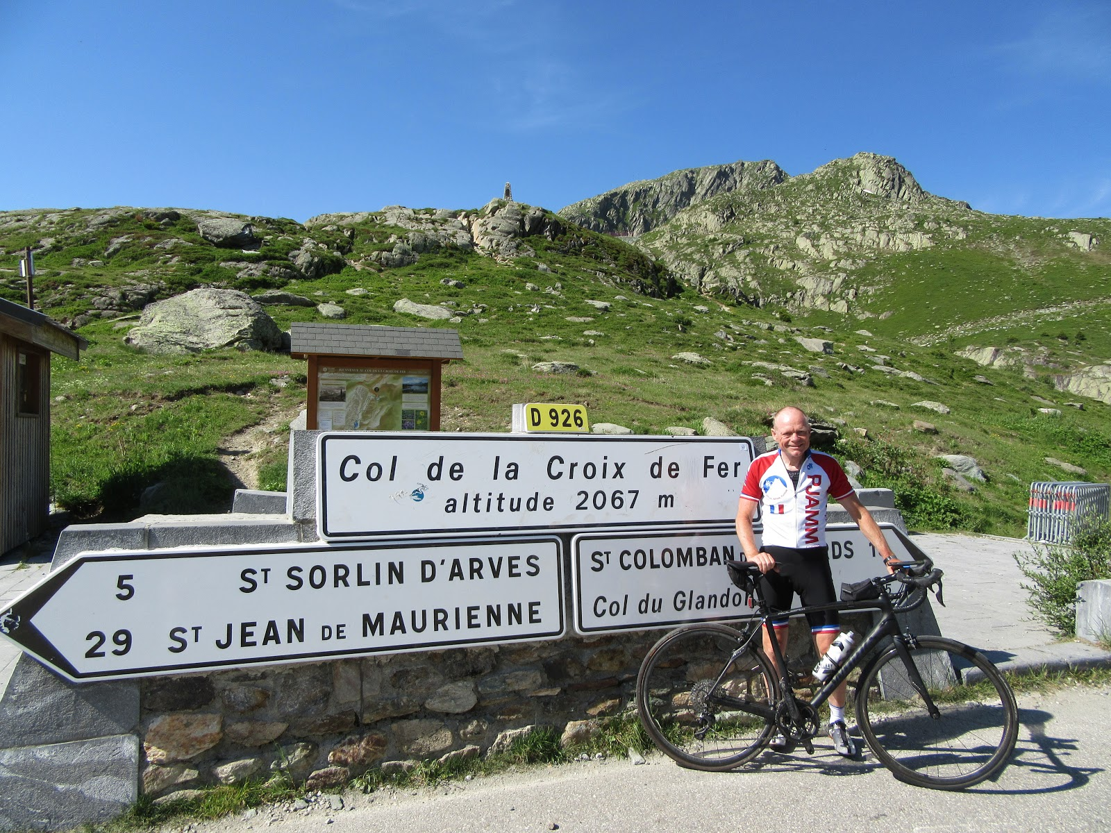 Cycling Col de la Croix de Fer, West  - John Johnson of PJAMM Cycling at Col sign