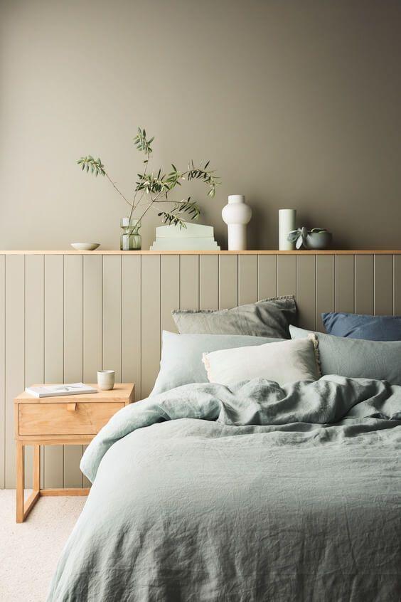 Quarto de casal com decoração simples cabeceira da cama de madeira cinza e parede de fundo cinza e criado mudo pequeno de madeira.