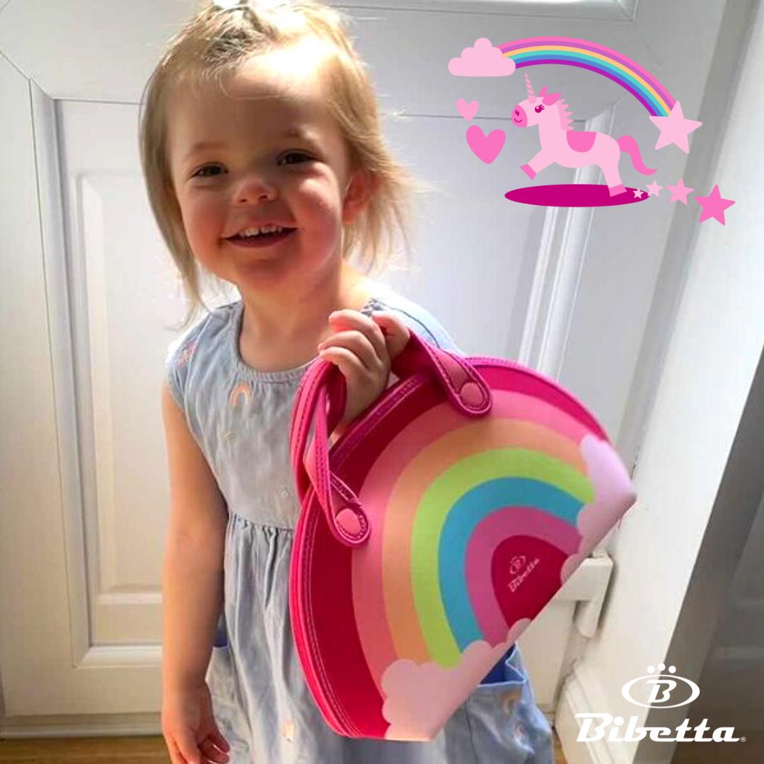Little girl holding a Bibetta Rainbow neoprene lunch bag