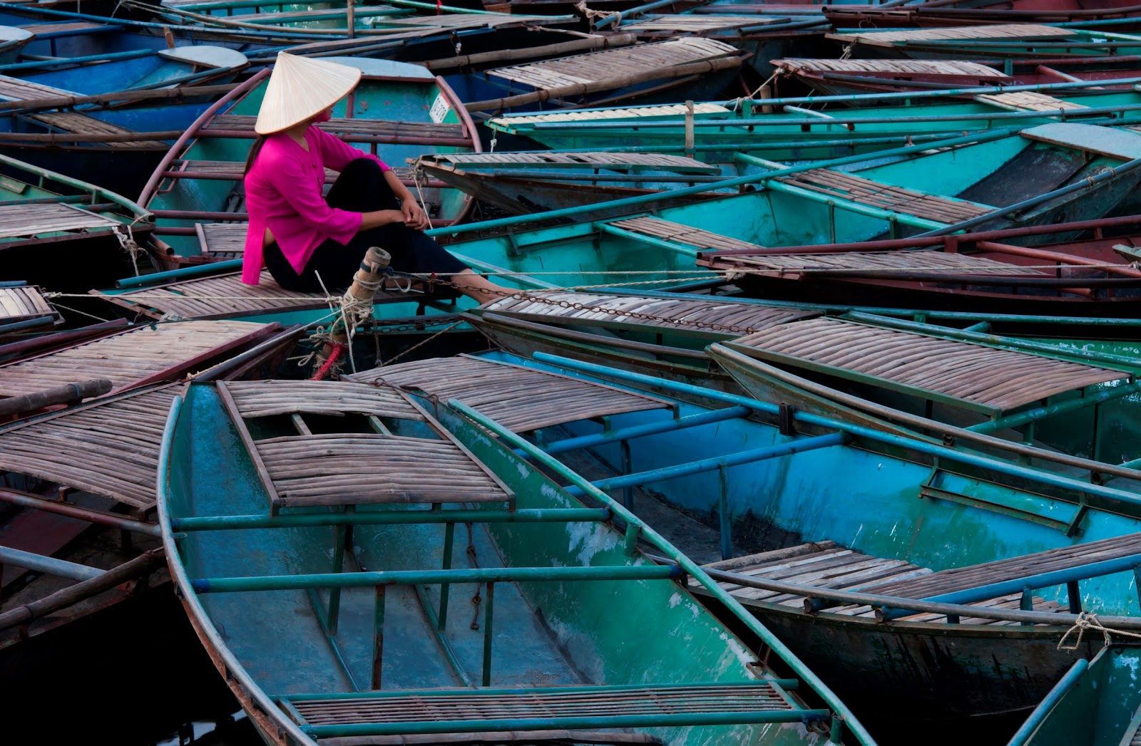 woman-sitting-among-raft-of-boats