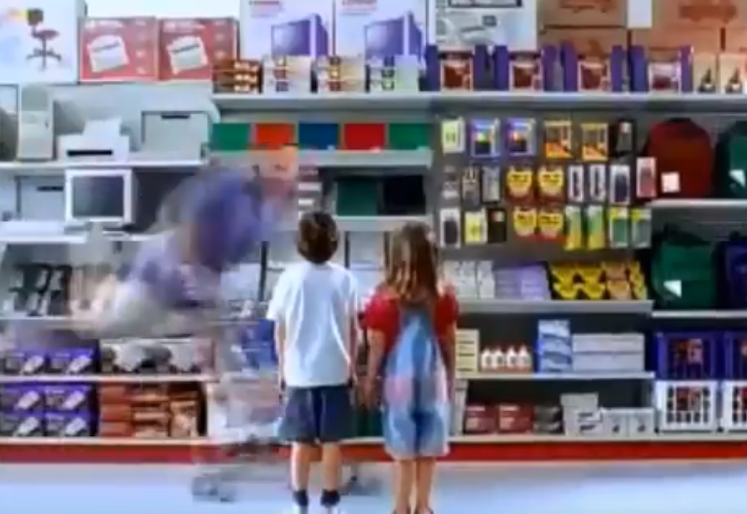 Sad brother and sister face towering shelves of school supplies while father gleefully glides through the store as he pushes the cart