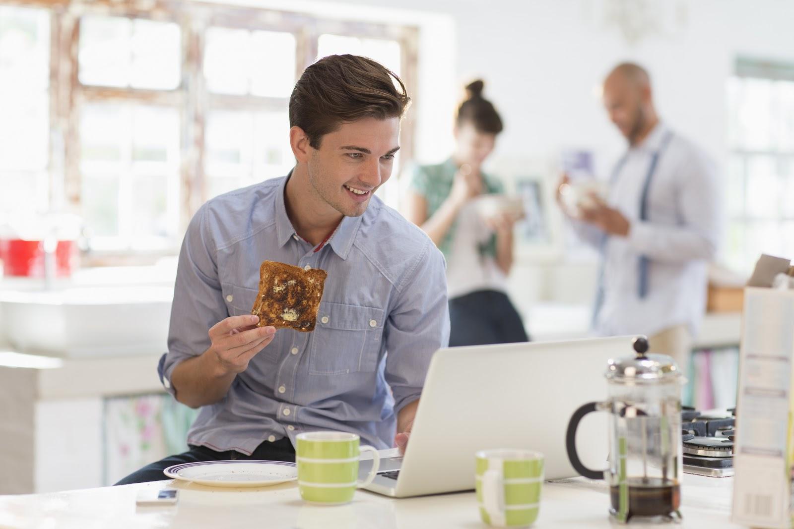 Um homem olhando para seu notebook e comendo uma torrada.