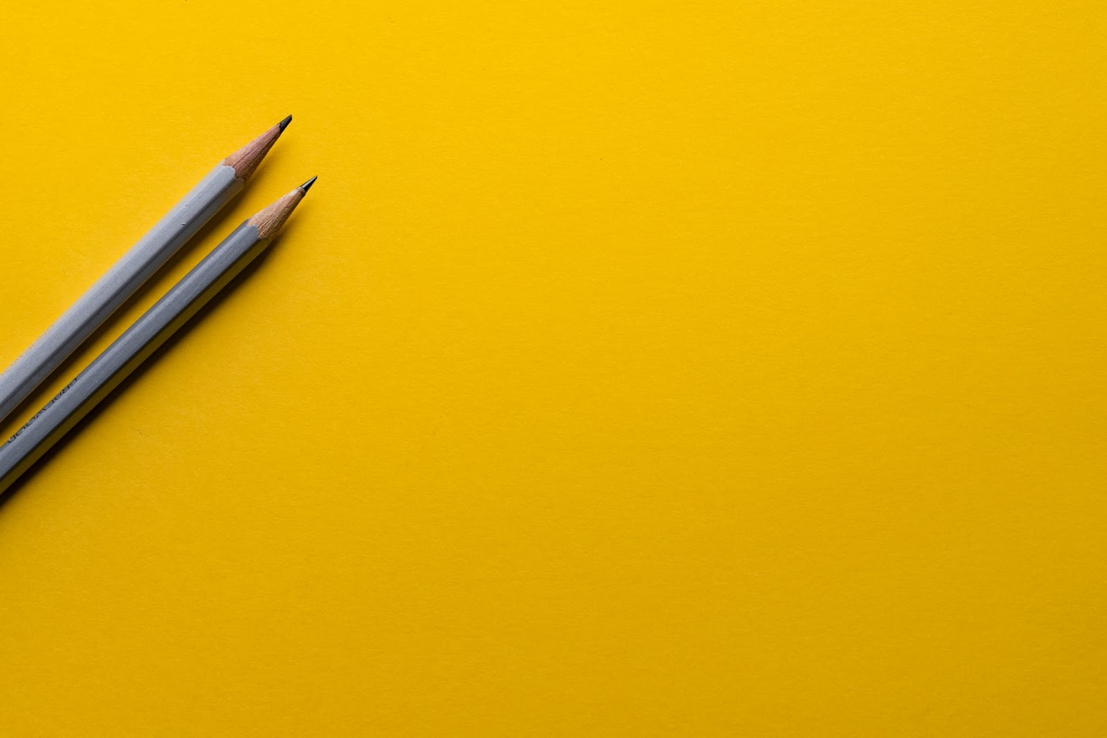 Two pencils on yellow paper. Creating a content calendar is essential to any good content strategy for bloggers.