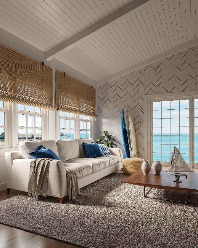 Quarto de madeira branca, com piso e mesinha de centro amadeirado, sofá branco com almofadas azuis, parede principal com revestimento branco em formato de seta e detalhes dourados.