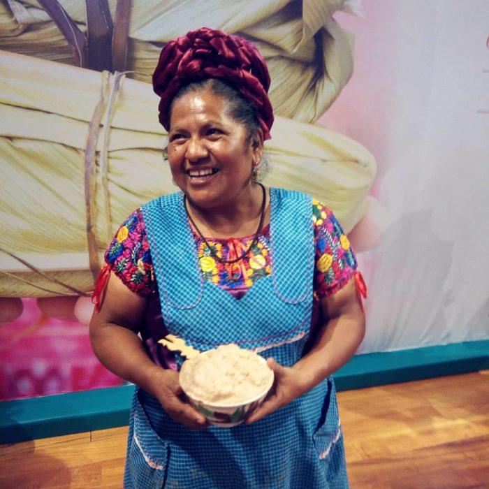 Abigail Mendoza mostrando frente a una pintura de un tamal y con un bowl en la mano