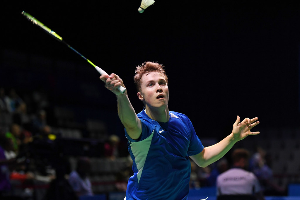 A male badminton player is stretching to make contact with an oncoming shuttle.