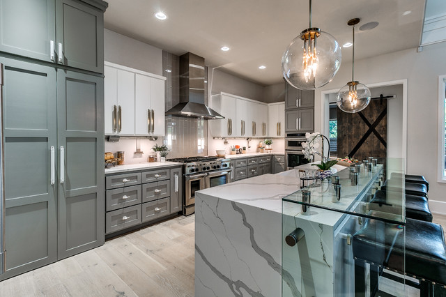 modern grey and white kitchen with white marble waterfall island countertop, shaker cabinets and glass globe pendant lighting