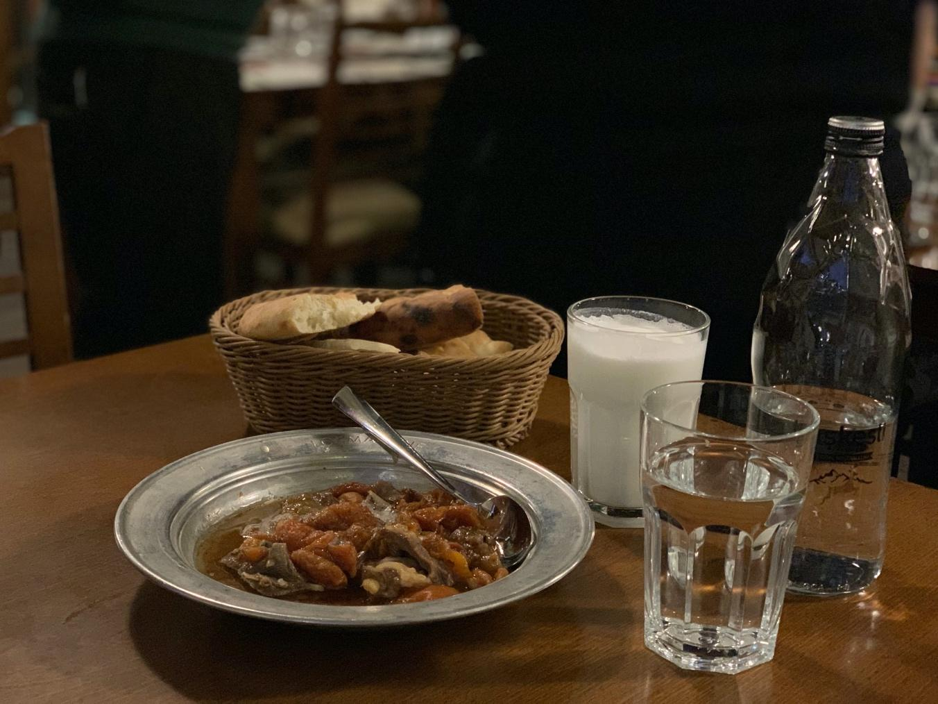 A plate of food and a glass of beer on a table  Description automatically generated