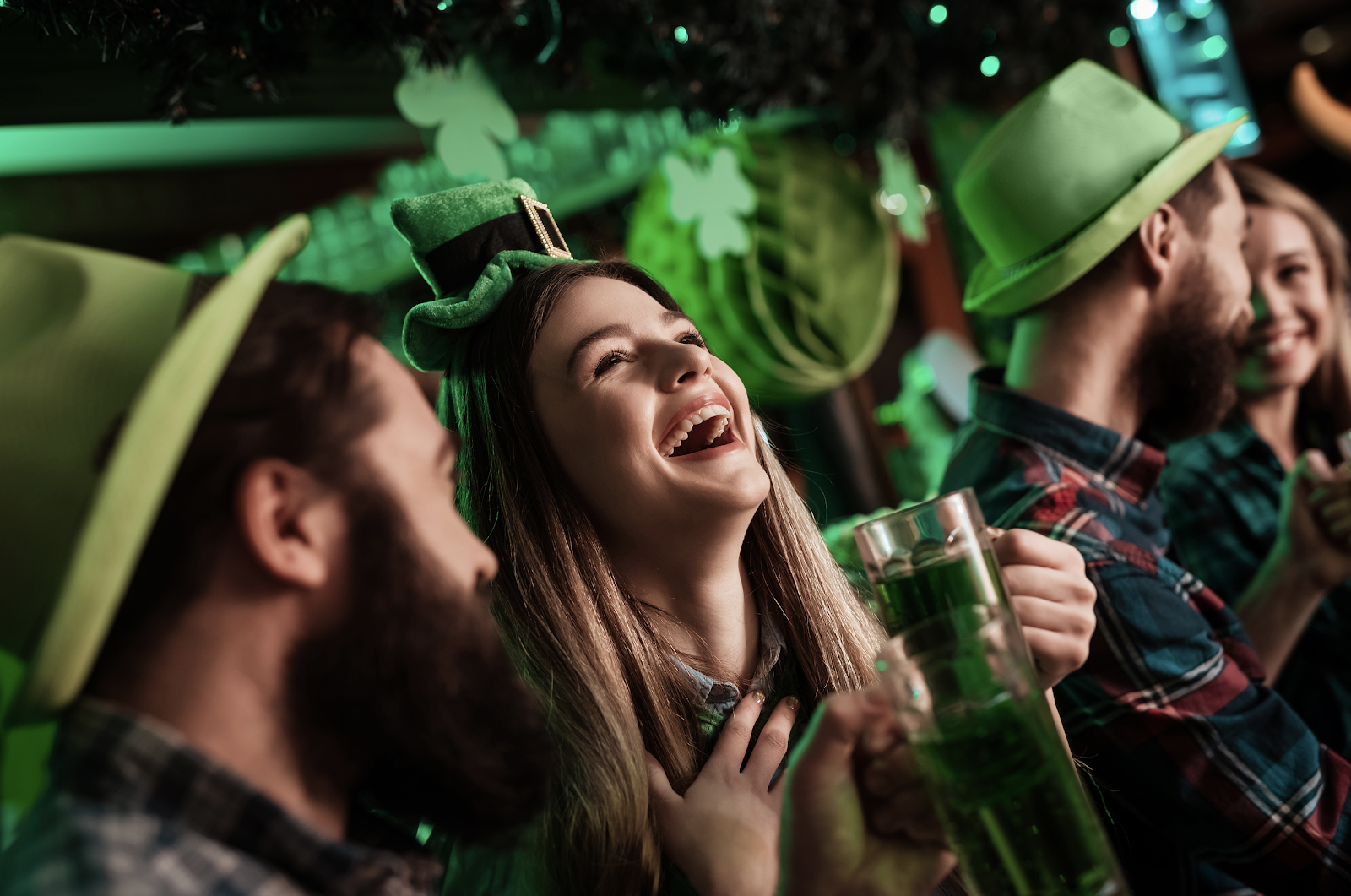 friends celebrating st. patrick's day in a bar wearing green hats and green beer and are laughing
