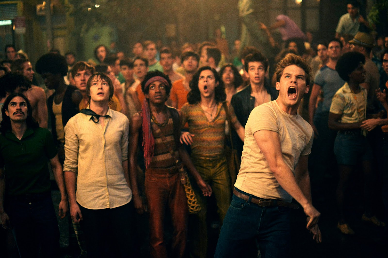 Still from Stonewall (2015). A crowd of young gay men stand in a dark street, looking up into the sky as the man standing furthest forward, Danny, throws something in a rage.