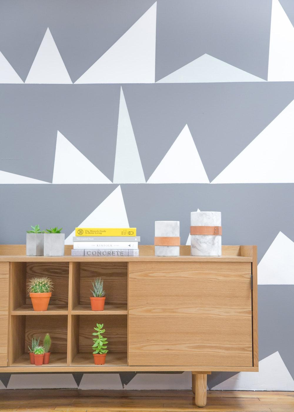 A desk with potted green plants and a stack of books near a wall with a geometric pattern
