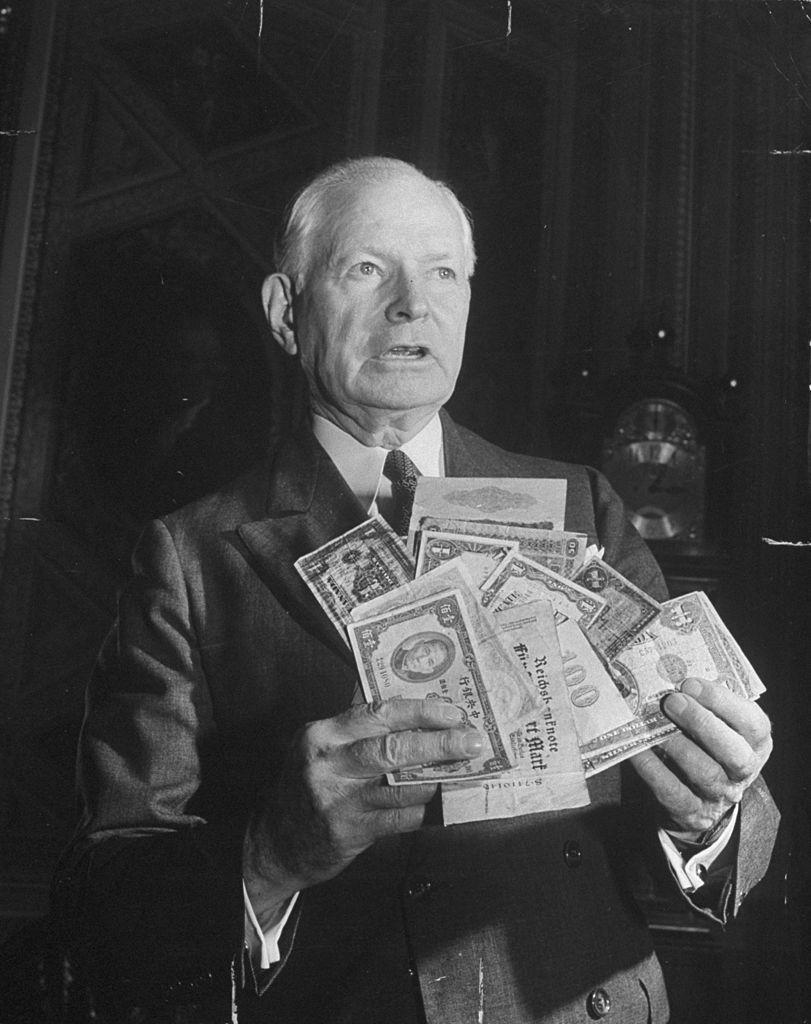 Homme montrant des monnaies au moment des accords de bretton woods