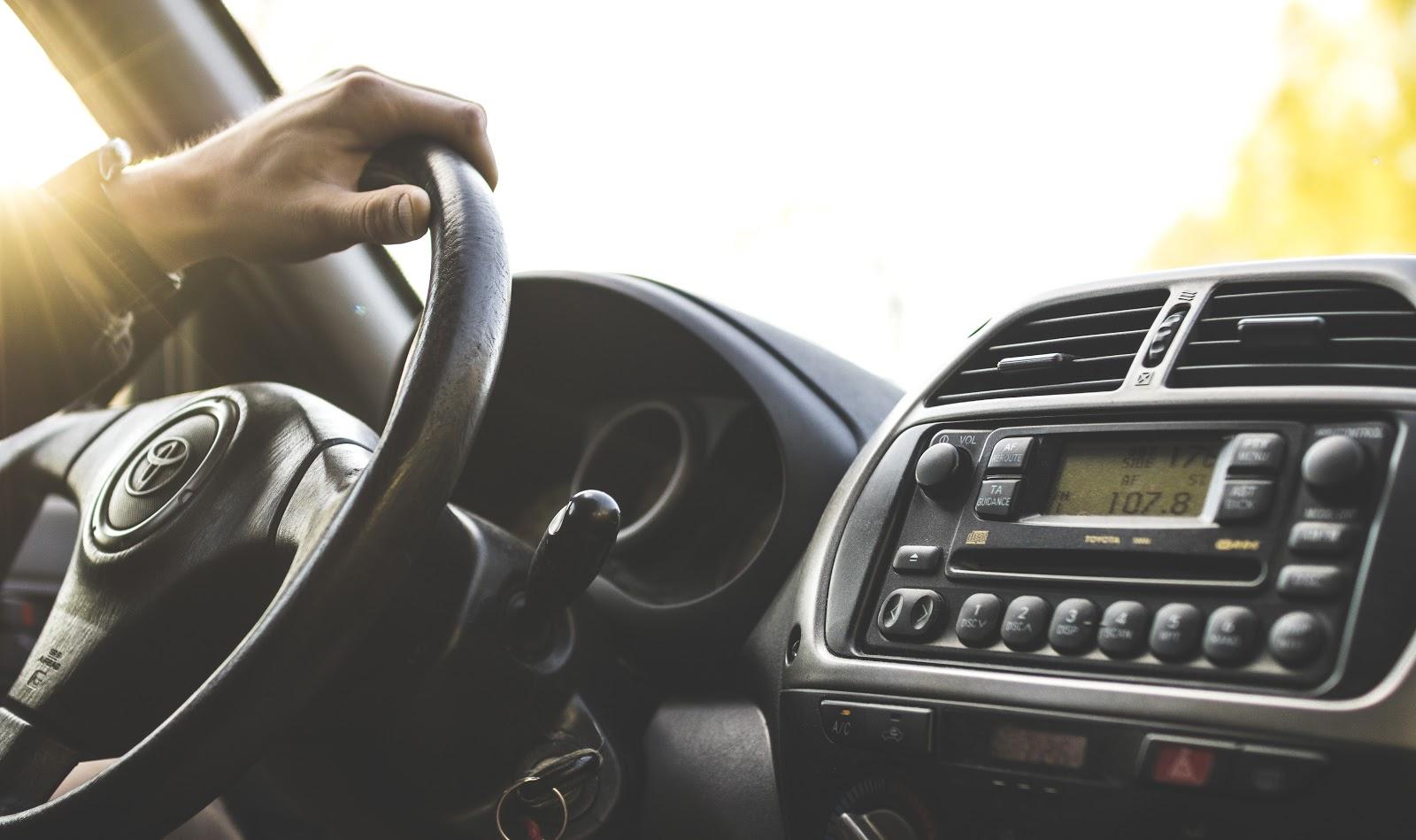 Uma pessoa com a mão no volante de um carro.