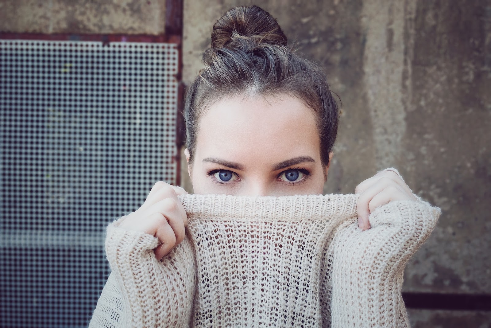 עיני אישה כחולות מביטות מבעד לסוודר