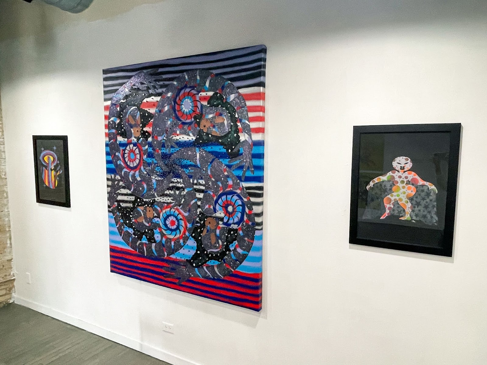 """Image: An installation view of won't you celebrate with me with three pieces in a row. The middle piece is """"Spinning Satellites"""" by Erin LeAnn Mitchell. It is a large, colorful abstract piece with horizontal stripes in the background and swirls in the foreground. The two pieces on either side of it are of colorful figures on a black background. Courtesy of the artist and FLXST Contemporary."""