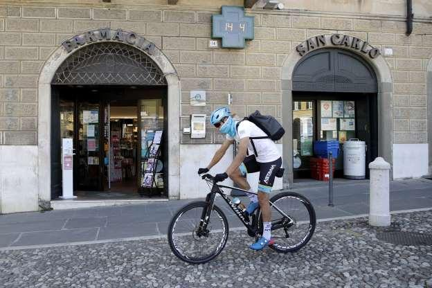 In this image taken on Tuesday, April 14, 2020, Italian professional cyclist Davide Martinelli, rides his bike after collecting medicine at a pharmacy to be delivered to residents in Rovato, near Brescia, Northern Italy. There are no fans lining the road. No teammates providing support. And no race to win. Professional cyclist Davide Martinelli has achieved a moral victory, though, by using his bike to help deliver medicine to elderly residents of his hometown in northern Italy during the coronavirus pandemic. (AP Photo/Luca Bruno)