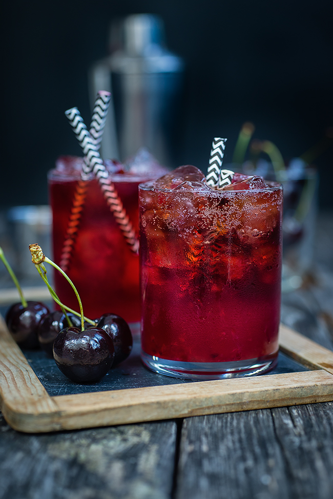 Cocktail served on the rocks garnished with cherries