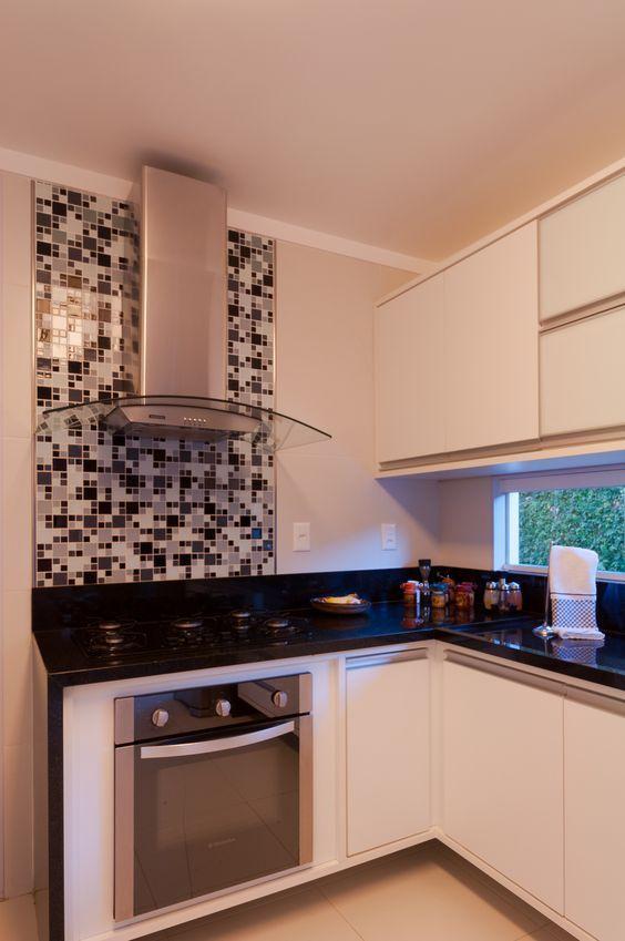 Cozinha com armários branco, bancada de mármore na pia, coifa e pastilhas preta e branca na parede da coifa.