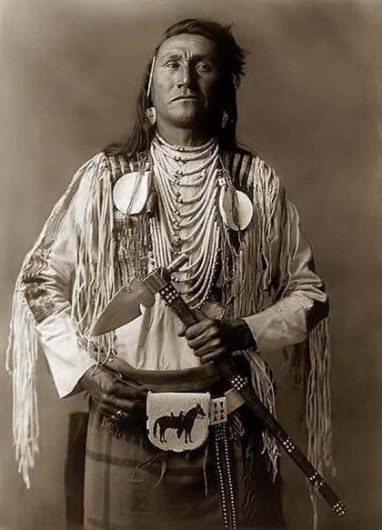 Un guerriero con un tomahawk con testa metallica e ornata