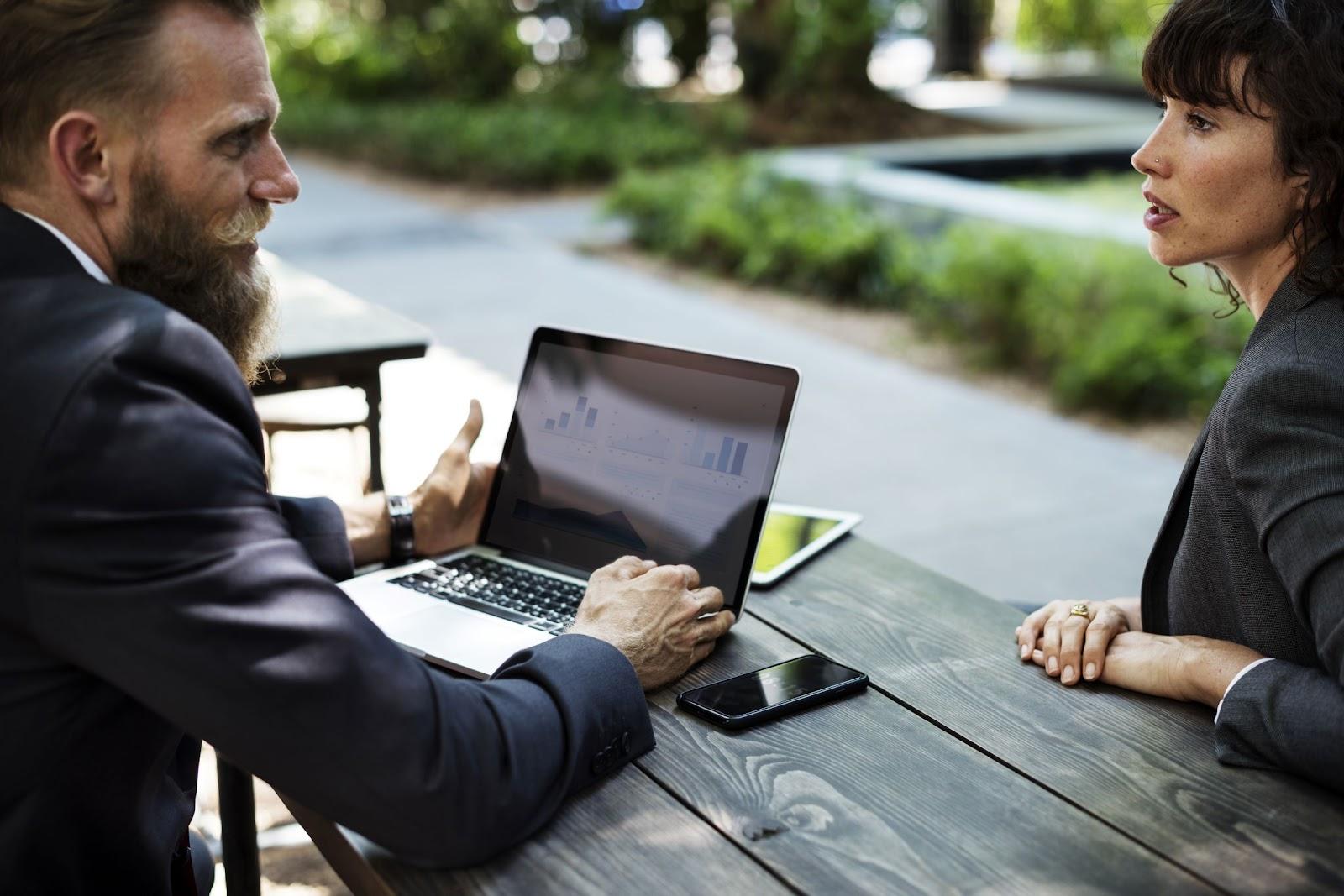 Foto da vista lateral de um homem e uma mulher do universo business trocando informações em uma praça de maneira remote everything utilizando SDN.