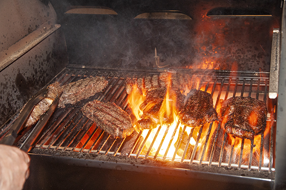 Several steaks grilling over a hot grill with flames.
