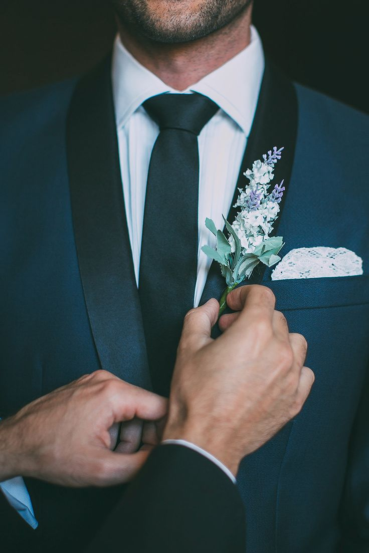 Close up of man with navy blue suit and flower boutinnere.