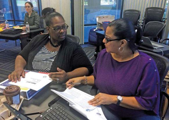 Two caregivers sitting next to each other at a desk, talking.