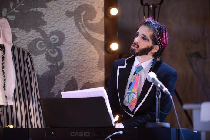 Image description: Amelia Cavallo is dressed as drag queen alter-ego Tito Bone. Tito is wearing a dark suit with a white shirt and brightly coloured graphic tie. Tito wears a full beard, striking purple eyeshadow and short, dark hair which is slicked back. Here, Amelia is performing as Tito on stage at a Casio keyboard with a microphone placed in front of her.