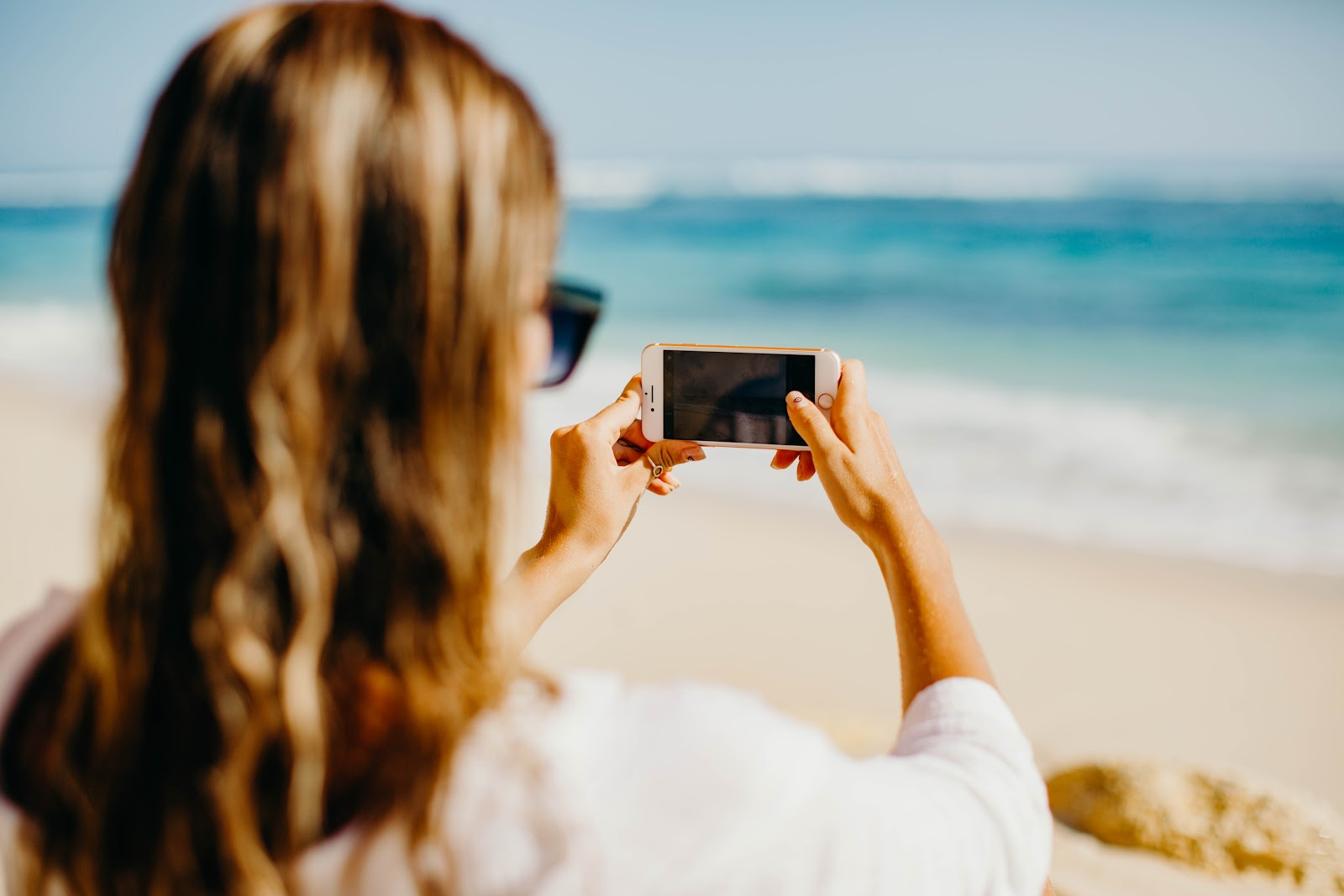 micro influencer holding phone to take a picture of the beach for campaign