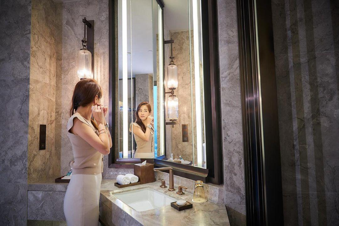 A Person Taking A Picture Of Herself In A Bathroom Mirror  Description Automatically Generated With Medium Confidence