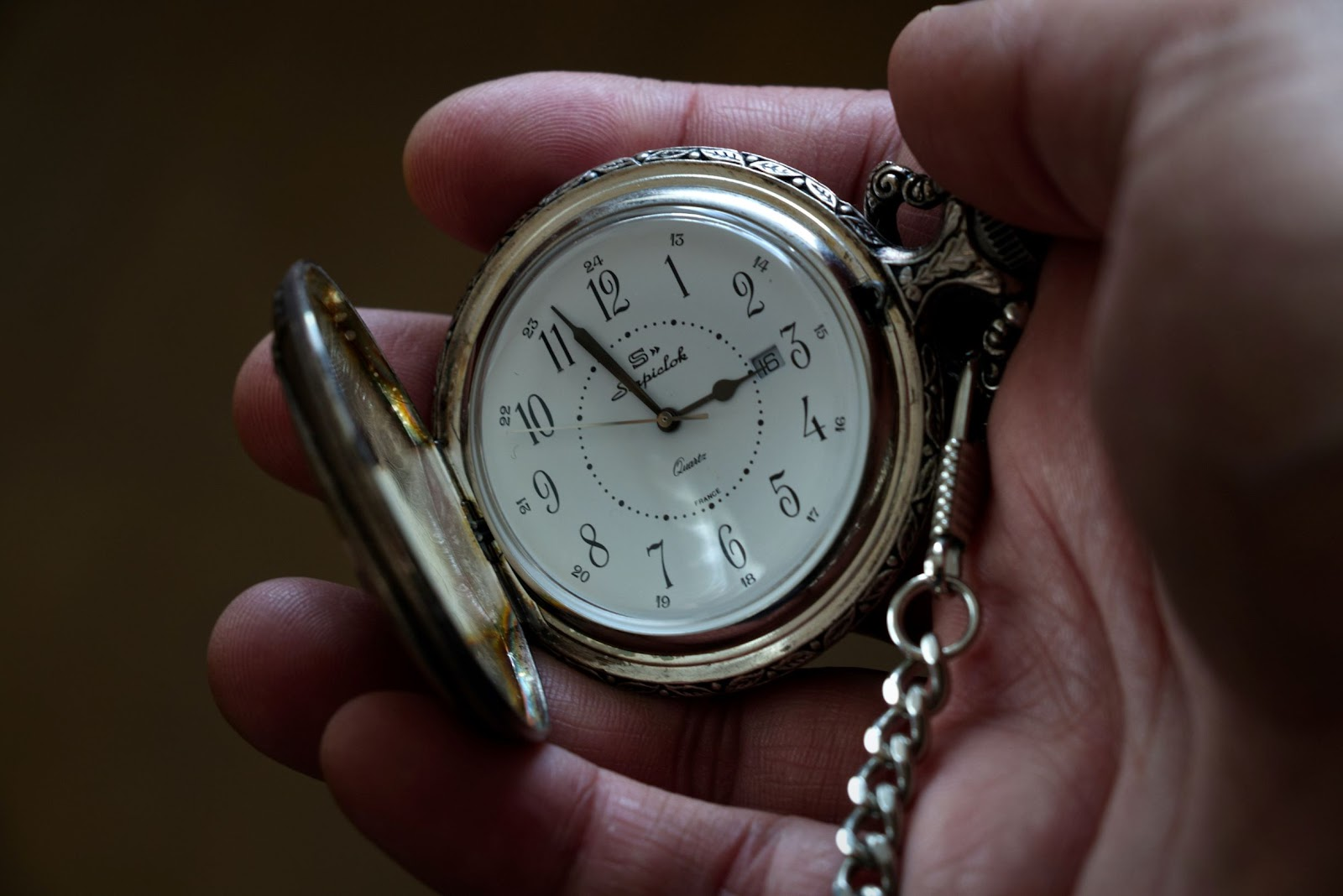 Hand holding old-fashioned wristwatch