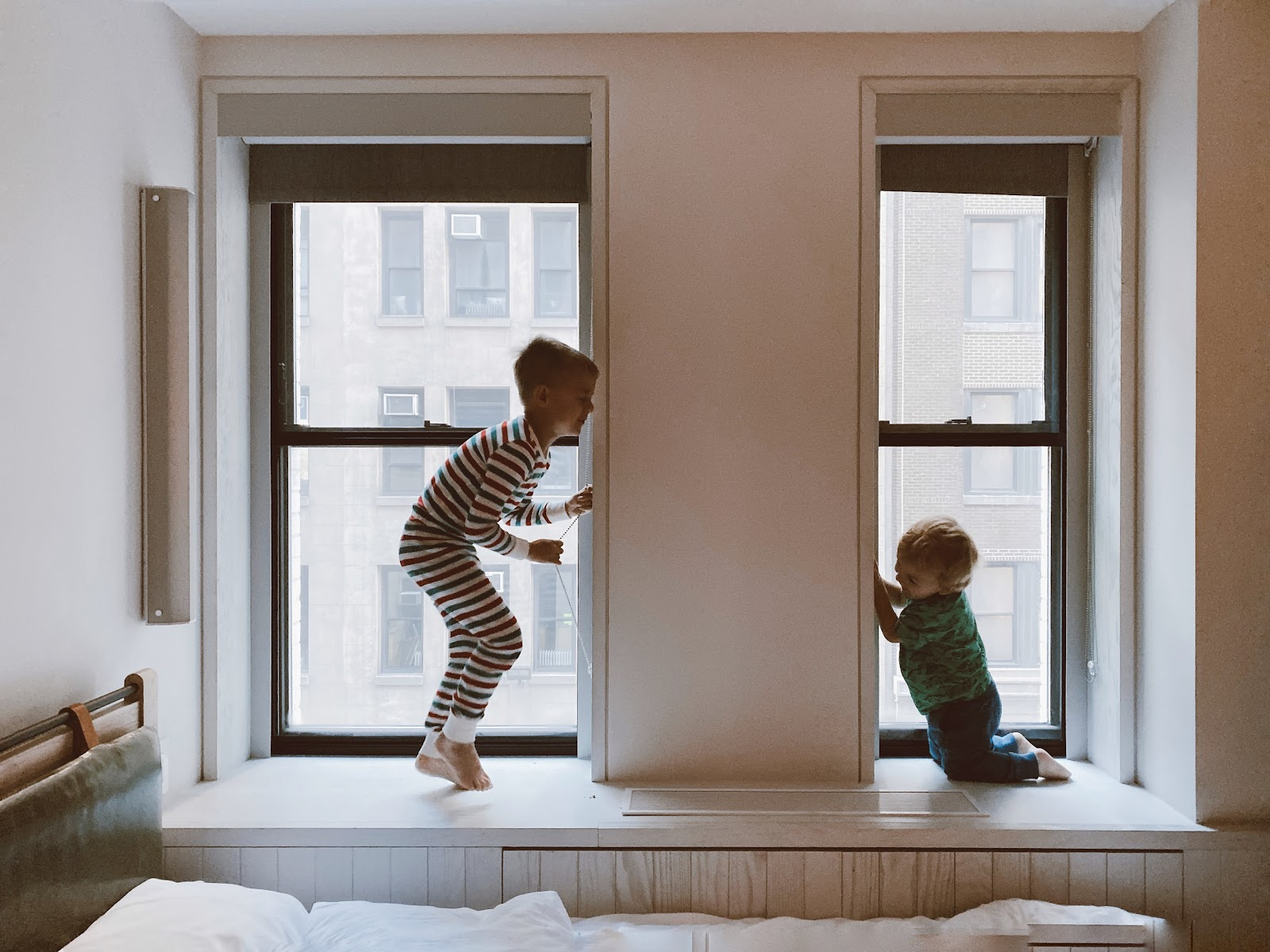 Two boys play in the window sills of their new home