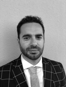 Foto en blanco y negro de un hombre con traje y corbata</p> <p>Descripción generada automáticamente