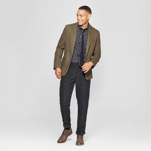 Individual posing while wearing an olive-green blazer with a patterned collard shirt and black pants