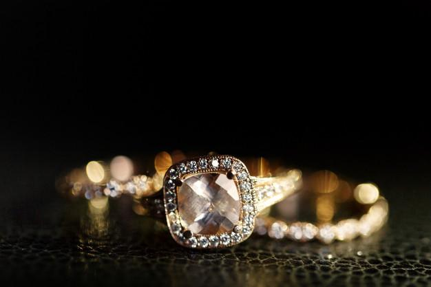 Jewels sparkle in the golden wedding rings lying on the leather Free Photo