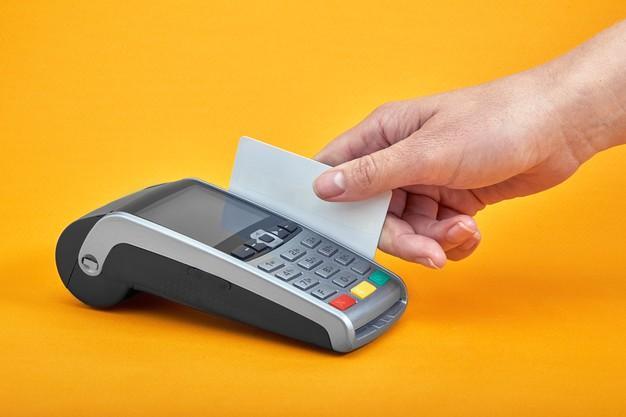 Close-up dos botões da máquina de pagamento com a mão humana segurando um cartão de plástico próximo na mesa amarela Foto Premium