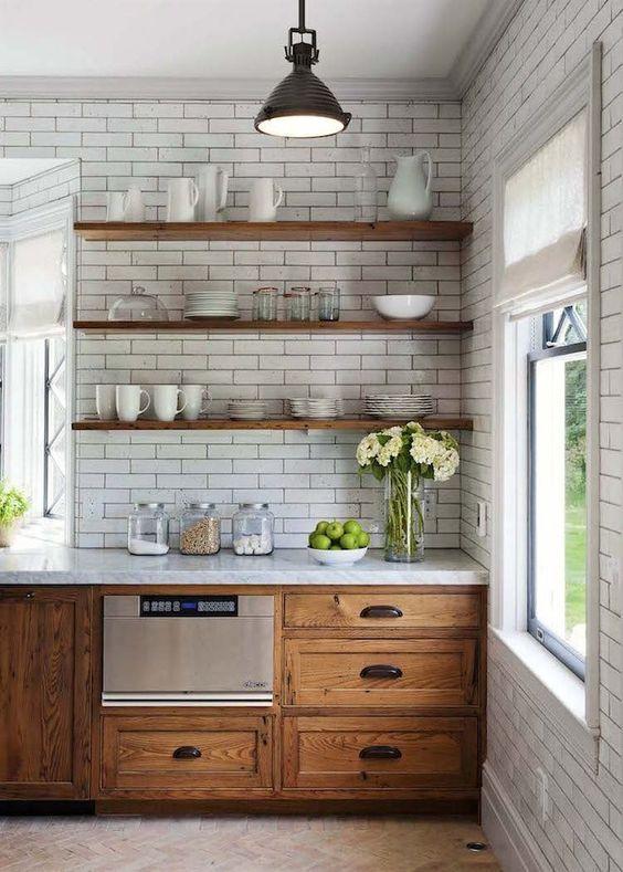 cozinha com paredes revestidas de azulejo subway tiles branco, com bancada da pia branca com armário antigo amadeirado, prateleiras de madeira com louças e piso de madeira claro