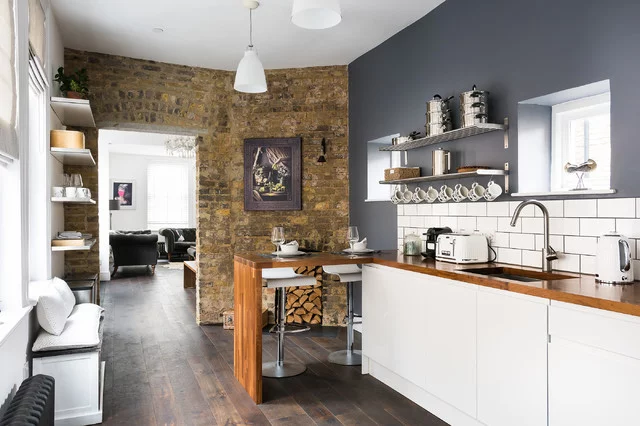 small farmhouse kitchen with exposed brick accent wall, dark wood floors, white base cabinets and wood countertops. the upper cabinets are replaced with open shelving to make the small room feel larger.