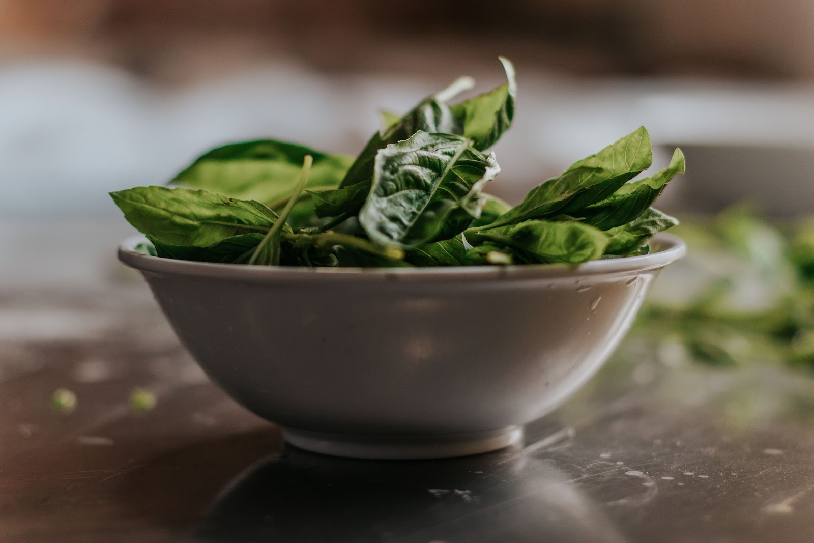 A bowl of raw spinach on a worktop.